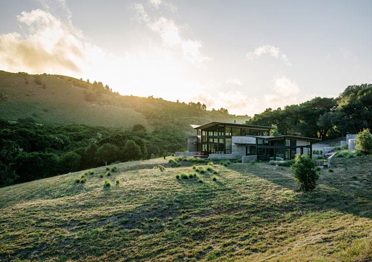 Стеклянный дом расположенный в окружении холмов